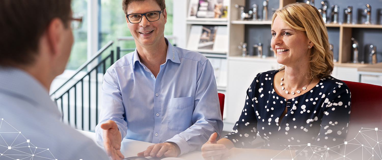 Zu sehen sind Kunden und der Geschäftsführer im Kundengespräch im hellblauen Hemd. Ein Ehepaar lässZu sehen ist Wolfgang Reichert, der Geschäftsführer, wie er ein Kundenpaar über Solarthermie und Heizungssanierung berät..