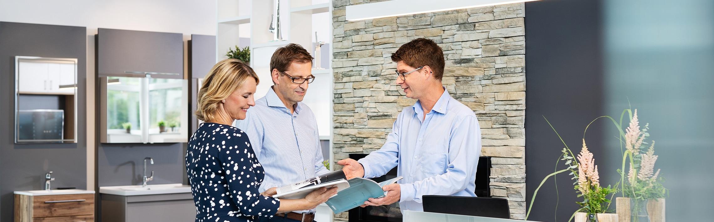 Zu sehen sind Kunden und der Geschäftsführer im hellblauen Hemd. Ein Ehepaar lässt sich gerade in den hellen, modernen Geschäftsräumen von Wolfgang Reichert persönlich beraten über eine Badsanierung und Heizungssanierung. Die blonde Frau blättert gerade in einer Broschüre.